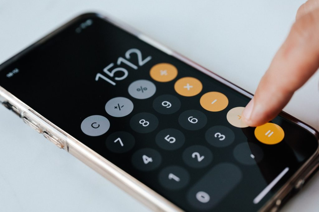 Persona digitando una suma en la calculadora de su móvil